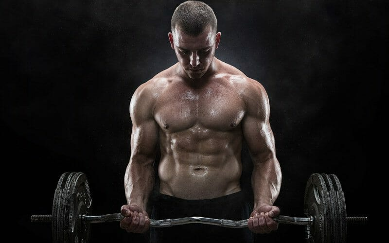 A man lifting weights on black background