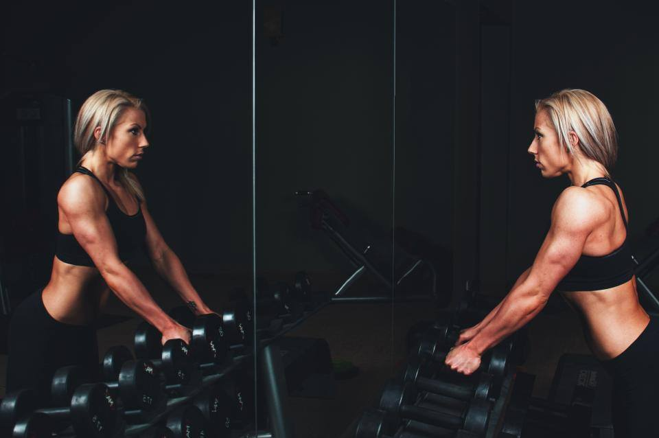 Woman with weights looking in the mirror