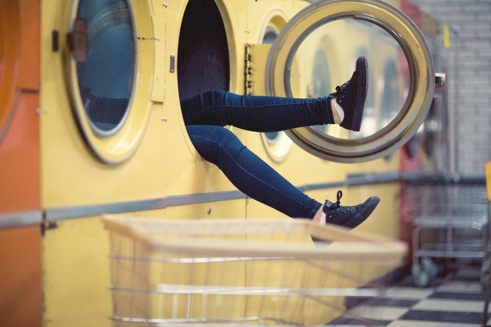 Women legs sticking out washing machine