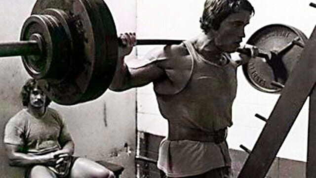 Arnold Schwarzenegger performing back squat