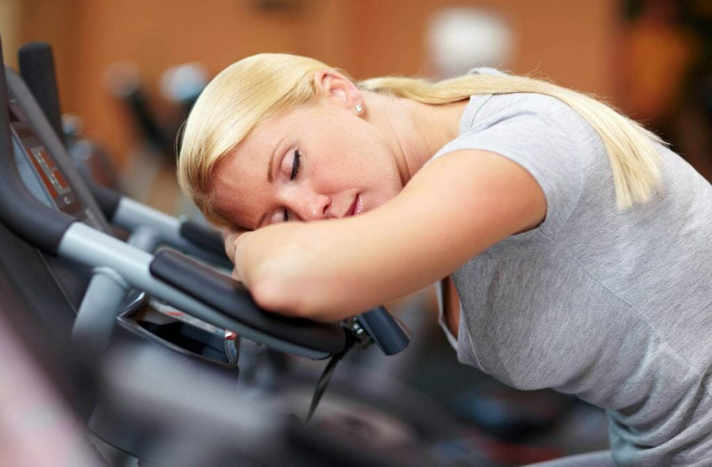 Tired woman sleeping in gym
