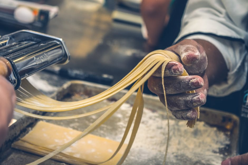 Man holding homemade pasta in his hand