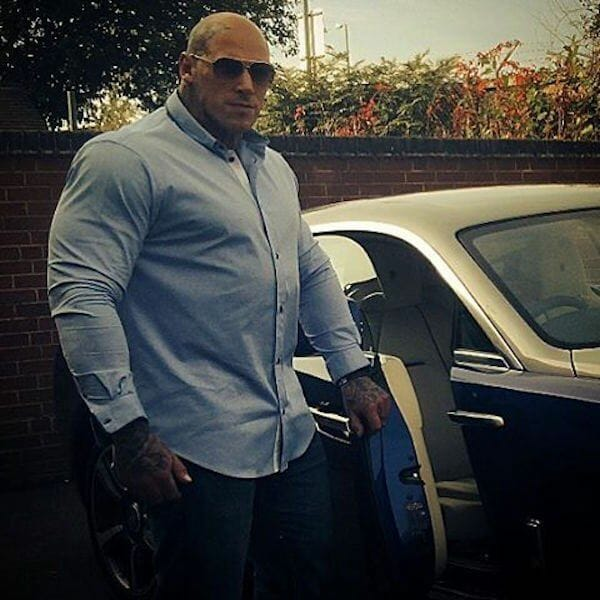 Man with huge muscles entering the car