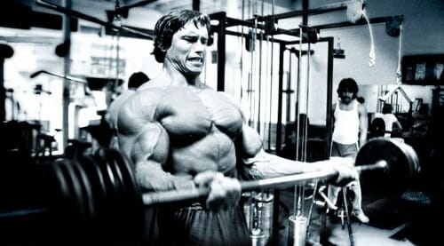 Black and white photo of Arnold Schwarzenegger at the gym