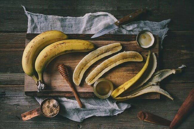 Bananas on a cutting board being prepared for a meal