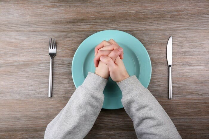 Man holding hands above empty plate