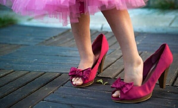 Girl walking in mom's pink shoes
