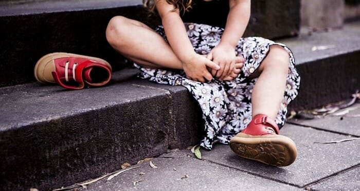 Little girl sitting on a step taking off her red shoes