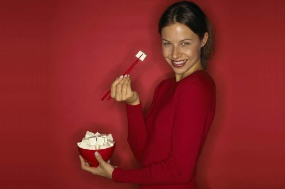 Happy woman eating tofu on a red background