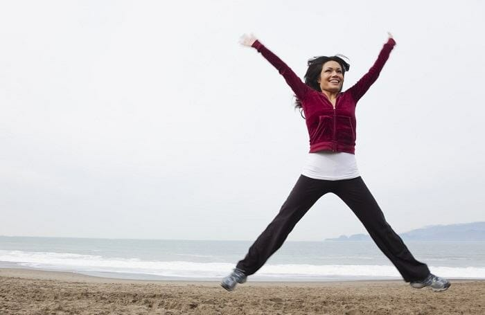 Woman doing jumping jacks on the beach