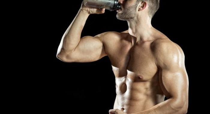 Man drinking weight gainer on black background