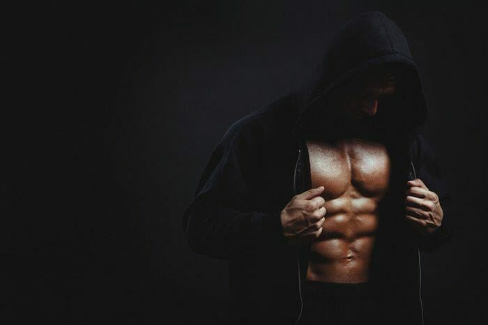 Man wearing black hood on black background