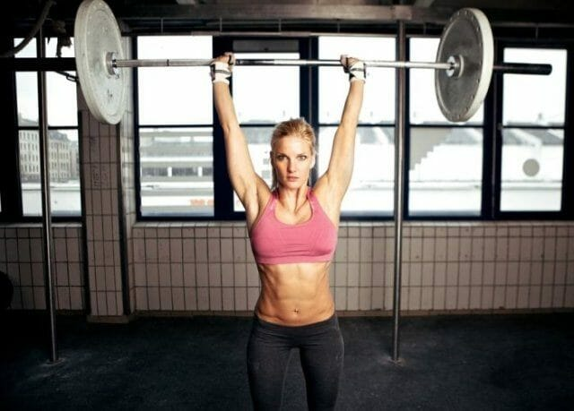 Woman doing military press - strength training