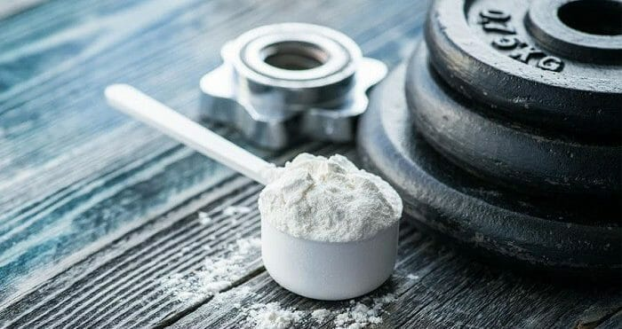 Creatine powder next to weights on wooden surface