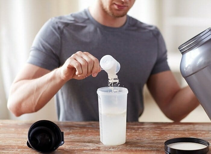 Young man using protein powder to make his beverage