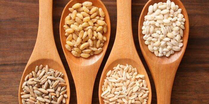 Different types of whole grains in a spoon
