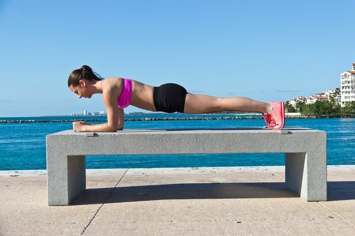 Woman doing plank on a bench next to the see