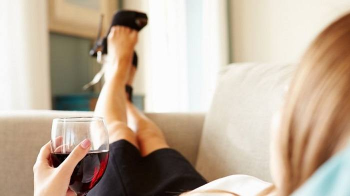 Woman lying on bed with a cup of wine in hand