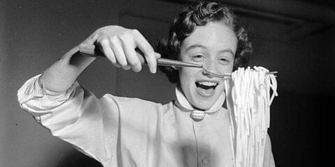 Black and white photo of a woman holding pasta