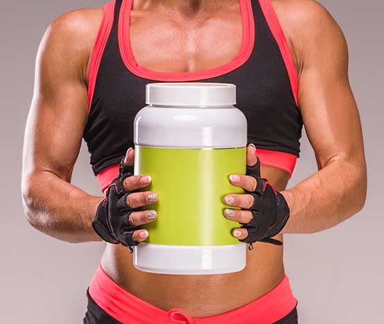 fit woman holding a bottle of creatine vs whey protein powder