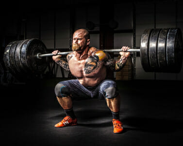 man holding a heavy barbell