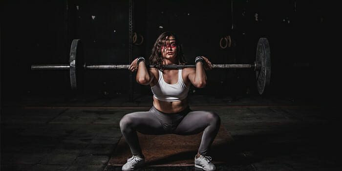 photo-of-a-woman-doing-barbell-squats