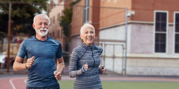 Two elderly jogging outside an empty sports ground
