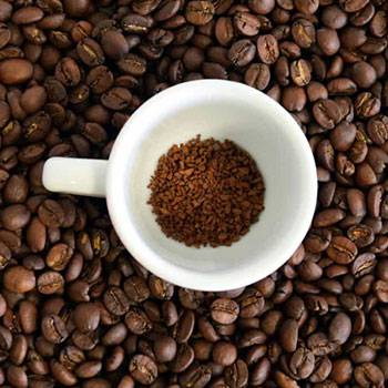 coffee powder in white cup over coffee beans