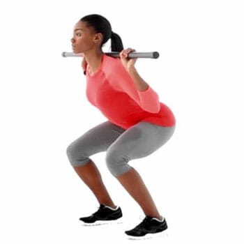 woman doing back squats with a body bar