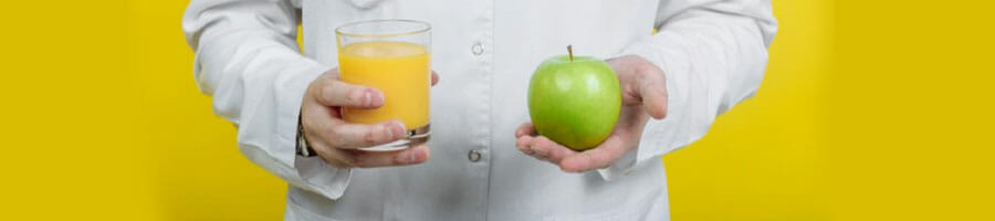 person holding juice and apple