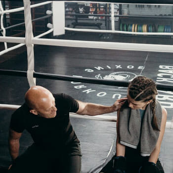woman with her coach in a boxing ring