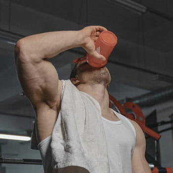 man drinking from a tumbler