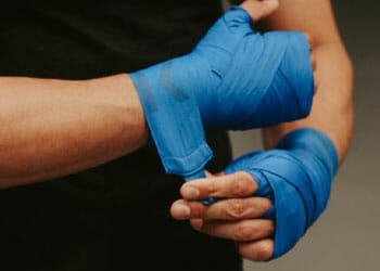 man fitting his boxing gloves