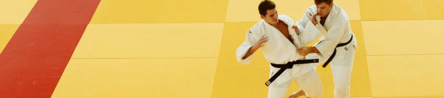 Two athletes performing judo in an open space