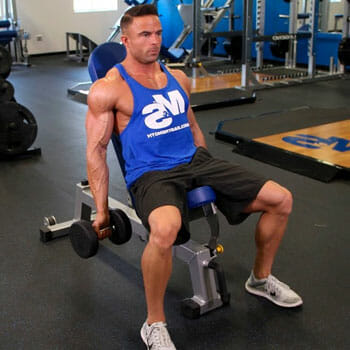 man sitting on a bench in a gym