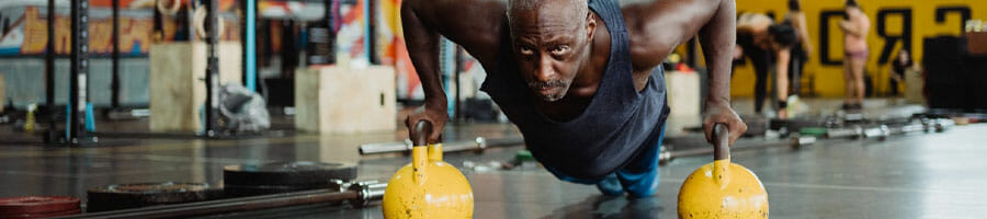 black man performing a push up row in a gym