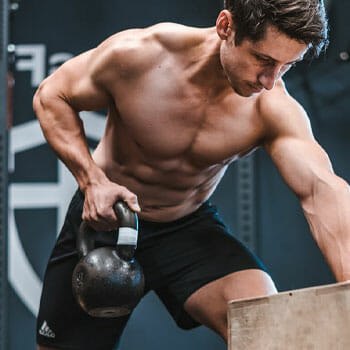 man working out with a kettle ball
