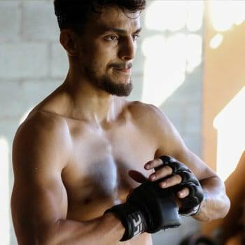 shirtless man adjusting his boxing gloves
