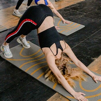 A woman doing a stretch in a yoga mat