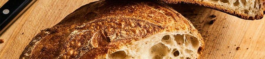 Half sliced sourdough bread on top of a chopping board