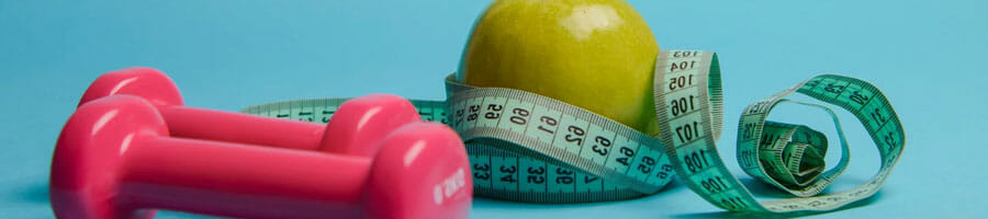 pink dumbbells, a measuring tape and a green apple