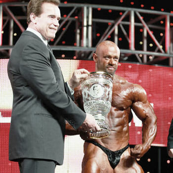 arnold handing a trophy to branch on stage