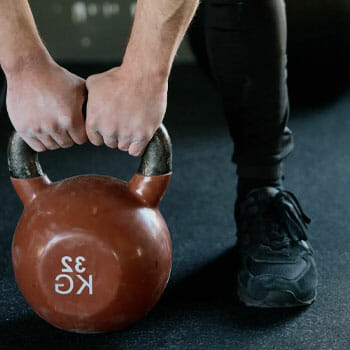 man pulling up a kettlebell with two hands