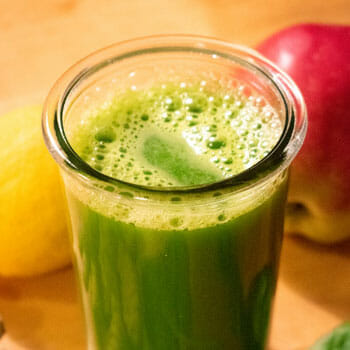 close up image of a green smoothie in a glass