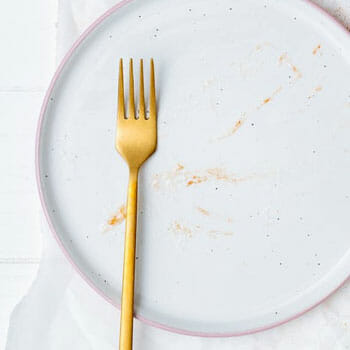 dirty white plate with a golden fork