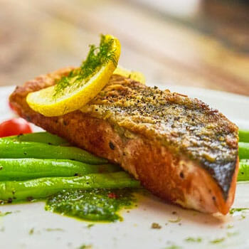 close up image of a cooked salmon with beans and lemon slice