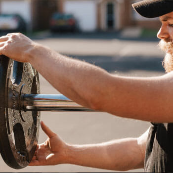 man fixing a barbell plate