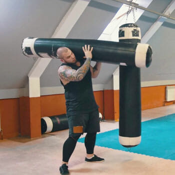 man lifting a heavy bag inside a gym