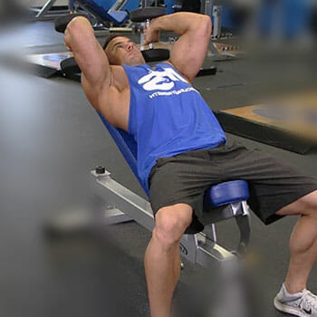 man in a incline gym bench lifting dumbbells
