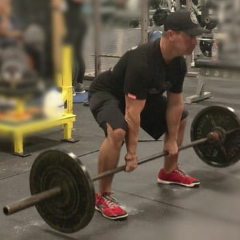 man inside a gym lifting a heavy barbell